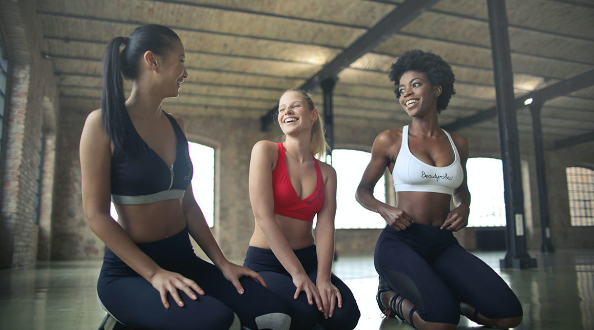 3 women sitting down in a group fitness class