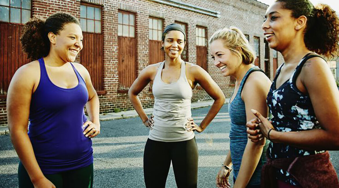 a group of diverse middle-aged women outside a gym wearing workout clothes