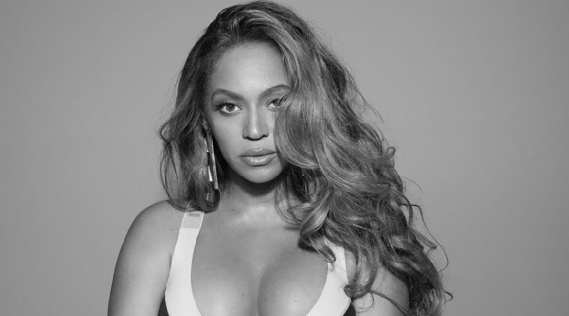 Beyonce standing in a fitness top against a gray background