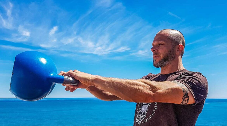 A man exercising with a kettle bell near an ocean